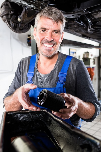 Mature male mechanic holding oil filter
